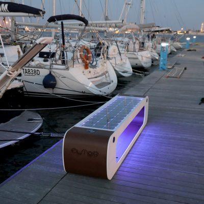 Modernus, išmanus lauko suoliukas su įdiegtais naujausiais technologiniais sprendimais uosto fone